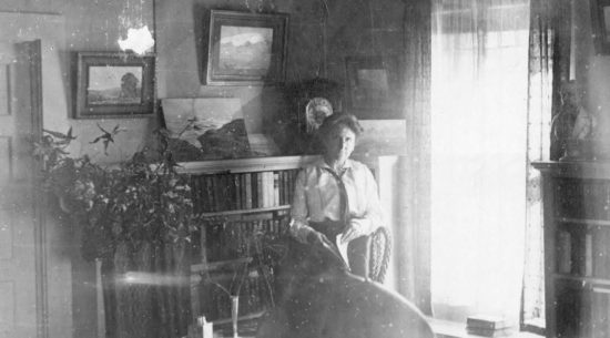 Effie Anderson Smithat home in Pearce, aroudn 1915. The paintings in this room were lost when her home burned in 1929.
